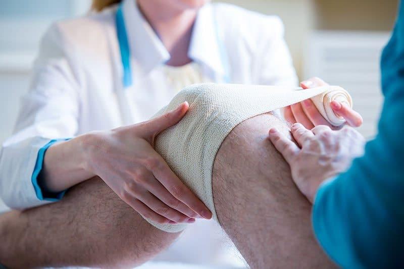 Nurse rewinding knee bandage